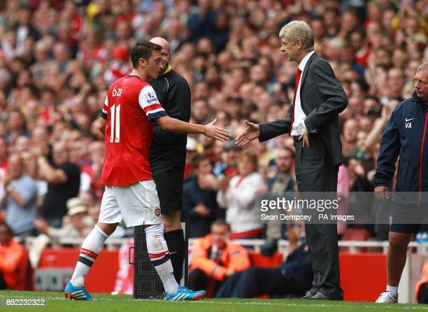 Arsenal's Mesut Ozil shakes hands with manager Arsene Wenger after being substituted
