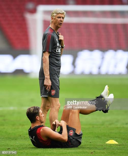 Arsenal's Mesut Ozil streches as coach Arsene Wenger looks on during a football training session in Beijing's National Stadium known as the Bird's...