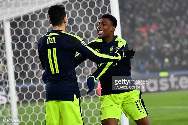 Arsenal's Nigerian forward Alex Iwobi celebrates after scoring a goal with his teammate Arsenal's German midfielder Mesut Ozil during the UEFA...