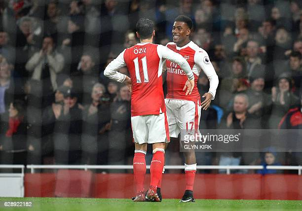 Arsenal's Nigerian striker Alex Iwobi celebrates with Arsenal's German midfielder Mesut Ozil after scoring their third goal during the English...