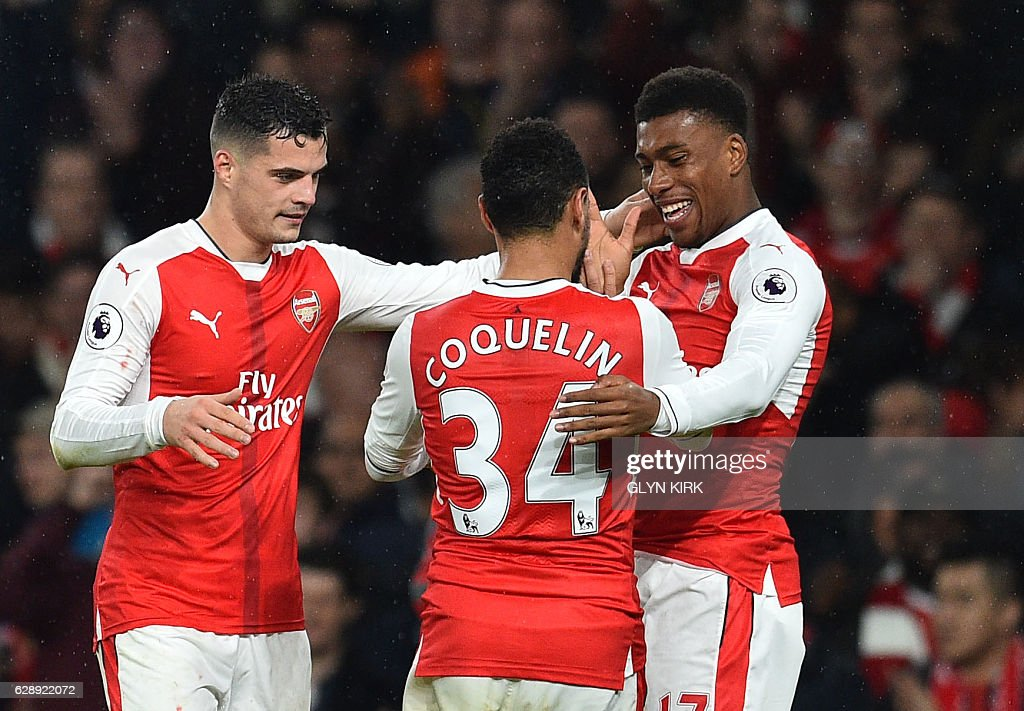 Arsenal's Nigerian striker Alex Iwobi (R) celebrates with teammates after scoring their third goal during the English Premier League football match between Arsenal and Stoke City at the Emirates Stadium in London on December 10, 2016. / AFP / Glyn KIRK / RESTRICTED TO EDITORIAL USE. No use with unauthorized audio, video, data, fixture lists, club/league logos or 'live' services. Online in-match use limited to 75 images, no video emulation. No use in betting, games or single club/league/player publications. /