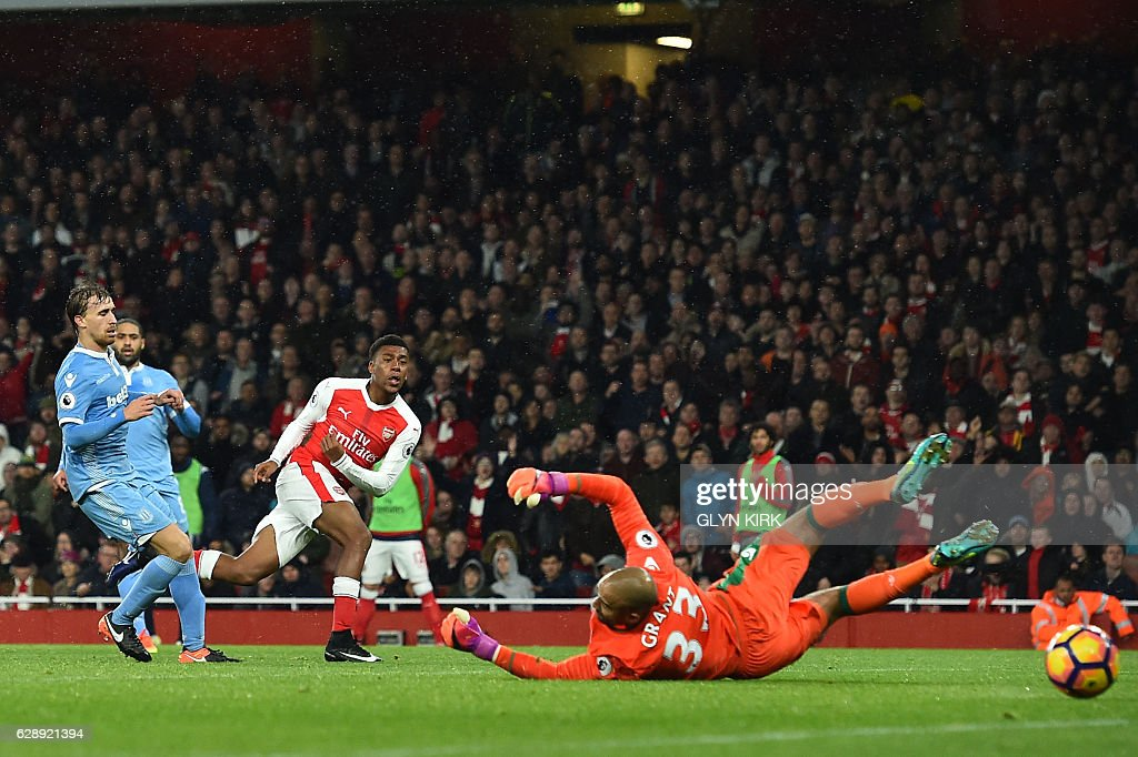 Arsenal's Nigerian striker Alex Iwobi (3L) shoots and scores past Stoke City's English goalkeeper Lee Grant during the English Premier League football match between Arsenal and Stoke City at the Emirates Stadium in London on December 10, 2016. / AFP / Glyn KIRK / RESTRICTED TO EDITORIAL USE. No use with unauthorized audio, video, data, fixture lists, club/league logos or 'live' services. Online in-match use limited to 75 images, no video emulation. No use in betting, games or single club/league/player publications. /