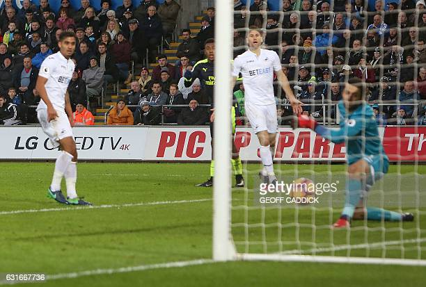 Arsenal's Nigerian striker Alex Iwobi watches a his shot ricocheted off Swansea City's English defender Kyle Naughton and past Swansea City's Polish...