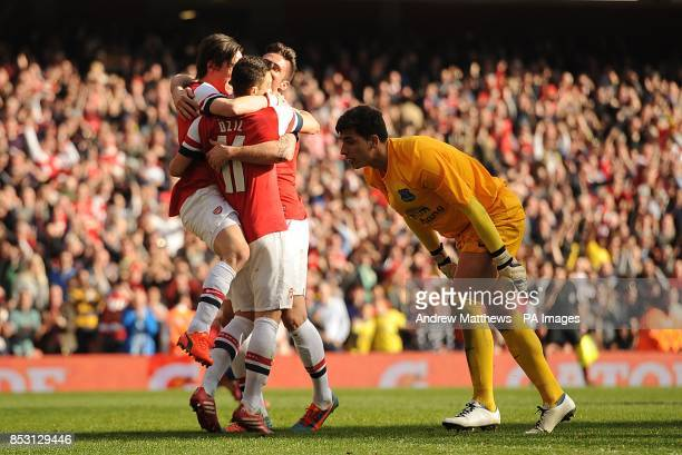 Arsenal's Olivier Giroud celebrates with his teammates after scoring his side's fourth goal of the game as Everton goalkeeper Joel Robles looks...