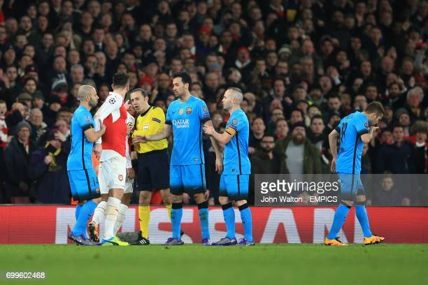 Arsenal's Olivier Giroud is held back by Barcelona's Javier Mascherano as he speaks to referee Cuneyt Cakir following an altercation with Barcelona's...