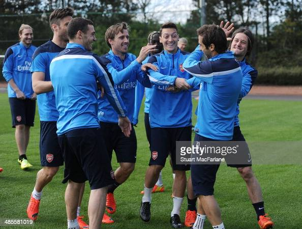 Arsenal's Olivier Giroud Thomas Vermaelen Nacho Monreal Mesut Ozil Mathieu Flamini and Tomas Rosicky mess around before a training session at London...