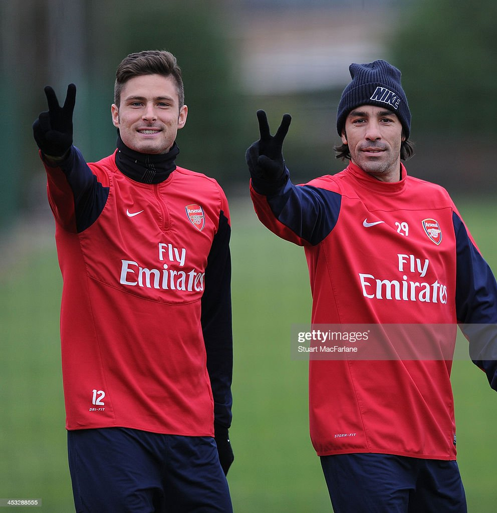 Arsenal's Olivier Giroud with ex player Robert Pires gesture before a training session at London Colney on December 3, 2013 in St Albans, England.