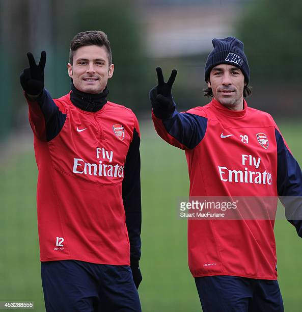 Arsenal's Olivier Giroud with ex player Robert Pires gesture before a training session at London Colney on December 3 2013 in St Albans England