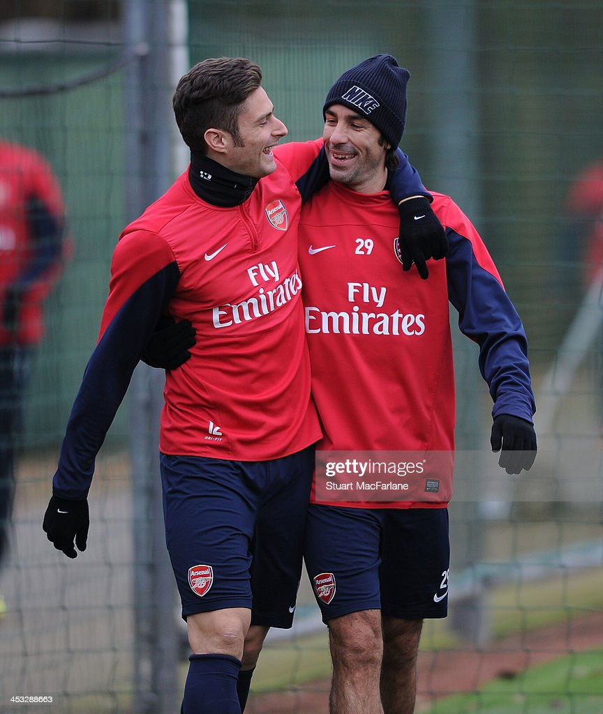 Arsenal's Olivier Giroud with ex player Robert Pires joke around before a training session at London Colney on December 3, 2013 in St Albans, England.