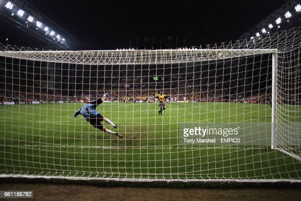 Arsenal's Patrick Vieira strikes his penalty against the bar as Galatasaray goalkeeper Taffarel goes the wrong way