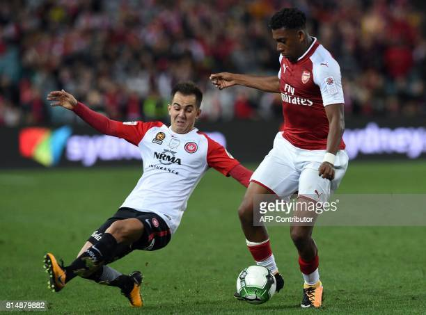 Arsenal's player Alex Iwobi fights for the ball with Steve Lustica of the Western Sydney Wanderers during their preseason football friendly played in...