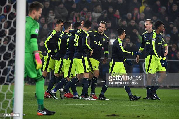 Arsenal's players celebrate after Arsenal's Spanish forward Lucas Perez scored a goal during the UEFA Champions league Group A football match between...