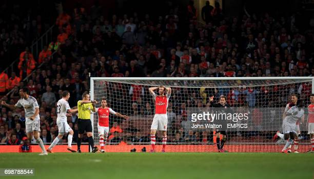 Arsenal's players including Per Mertesacker Santi Cazorla and goalkeeper David Ospina stand dejected after Swansea City's Bafetimbi Gomis scores his...
