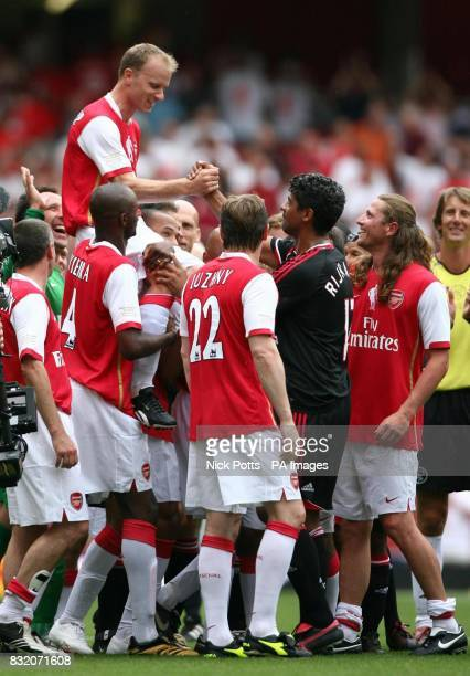Arsenal's players lift Dennis Bergkamp high on their shoulders as he shakes hands with Frank Rijkarrd following his Testimonial match against Ajax at...