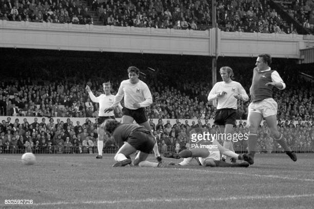 Arsenal's Ray Kennedy sweeps the ball past Nottingham Forest goalkeeper Jim Barron to score his team's second goal watched by teammate John Radford...