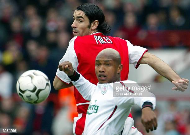 Arsenal's Robert Pires vies for the ball with ElHadji Diouf of Liverpool during their premier league clash at Highbury in London 09 April 2004 AFP...