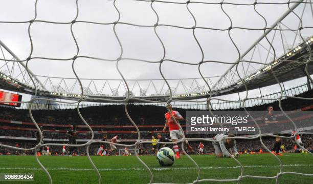 Arsenal's Santi Cazorla and Liverpool goalkeeper Simon Mignolet look on as Arsenal's Olivier Giroud scores their fourth goal