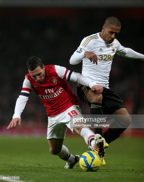 Arsenal's Santi Cazorla is tackled by Swansea's Wayne Routledge during the FA Cup Third Round Replay at the Emirates Stadium London