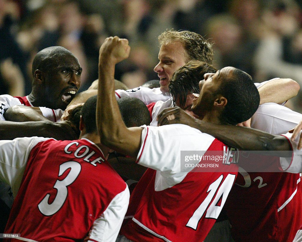 Arsenal's Sol Campbell (L), Dennis Bergkamp (C) and Thierry Henry (R) mobs Robert Pires celebrating his equalizer against Chelsea during their Champions league quarter final first leg clash at Stamford bridge in London,24 March 2004.