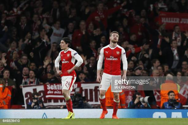 Arsenal's Spanish defender Hector Bellerin and Arsenal's German defender Shkodran Mustafi react after the third goal during the UEFA Champions League...