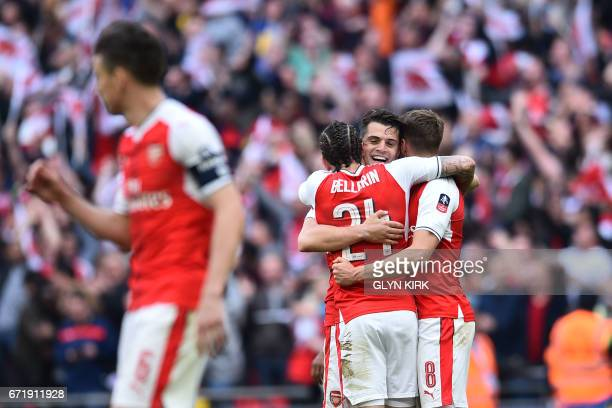 Arsenal's Spanish defender Hector Bellerin Arsenal's Swiss midfielder Granit Xhaka and Arsenal's Welsh midfielder Aaron Ramsey celebrate victory...