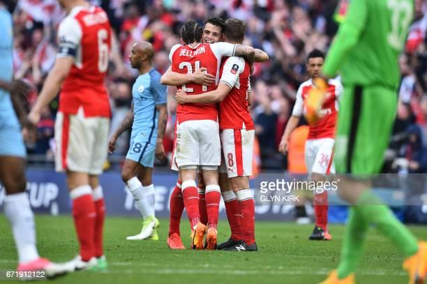 Arsenal's Spanish defender Hector Bellerin Arsenal's Swiss midfielder Granit Xhaka and Arsenal's Welsh midfielder Aaron Ramsey celebrate victory...