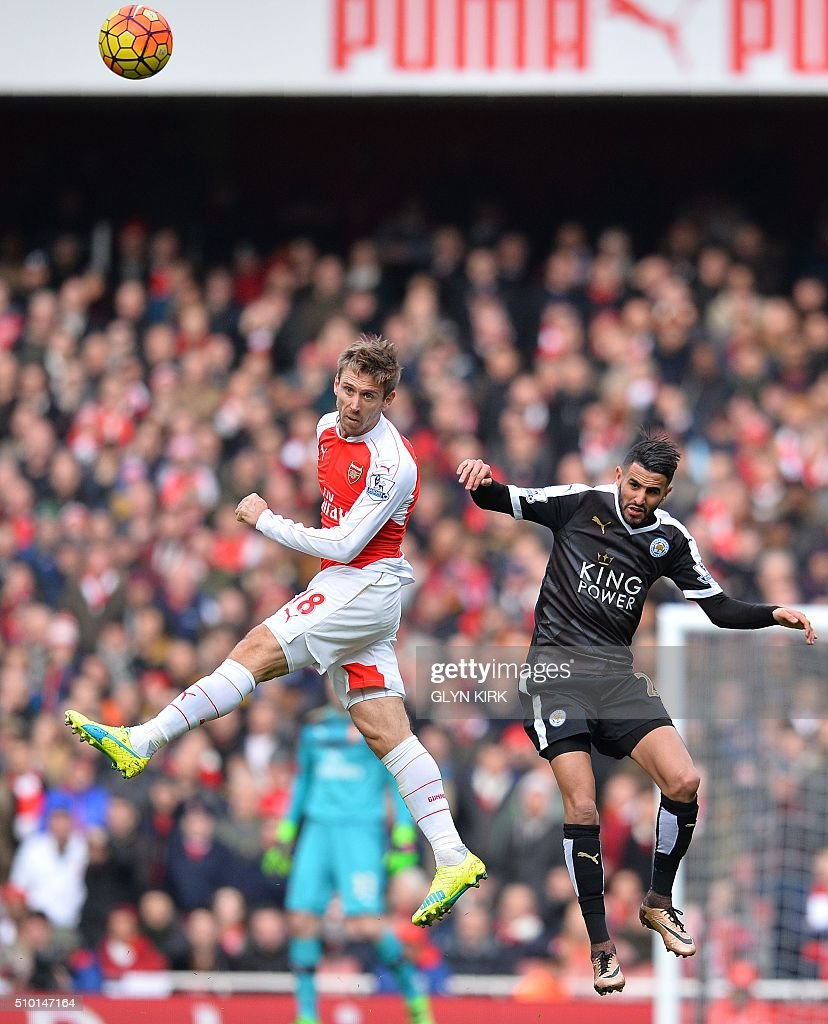 Arsenal's Spanish defender Nacho Monreal (L) vies in the air with Leicester City's Algerian midfielder Riyad Mahrez during the English Premier League football match between Arsenal and Leicester at the Emirates Stadium in London on February 14, 2016. / AFP / GLYN KIRK / RESTRICTED TO EDITORIAL USE. No use with unauthorized audio, video, data, fixture lists, club/league logos or 'live' services. Online in-match use limited to 75 images, no video emulation. No use in betting, games or single club/league/player publications. /