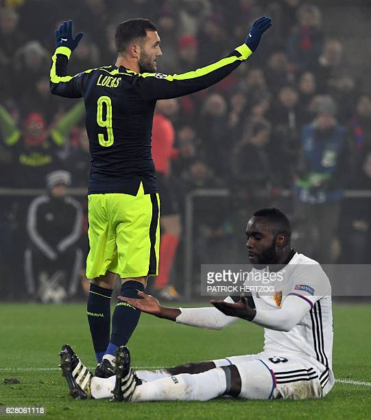 Arsenal's Spanish forward Lucas Perez celebrates after scoring a goal as Basel's Colombian defender Eder Balanta reacts during the UEFA Champions...