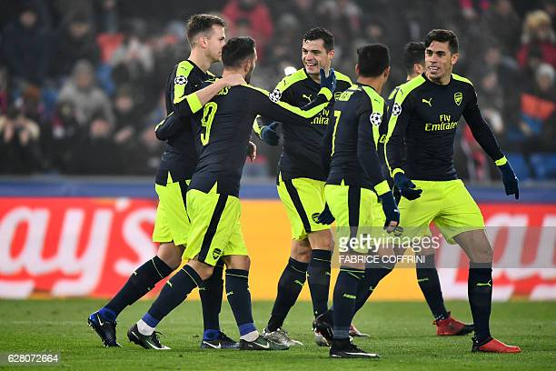 Arsenal's Spanish forward Lucas Perez celebrates after scoring a goal with his teammates during the UEFA Champions league Group A football match...