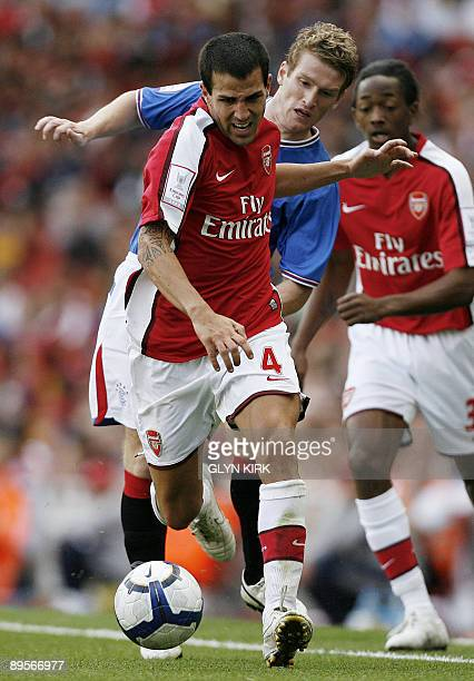 Arsenal's Spanish midfielder Cesc Fabregas goes past Rangers' Northern Irish midfielder Steven Davis during the Emirates Cup competition at the...