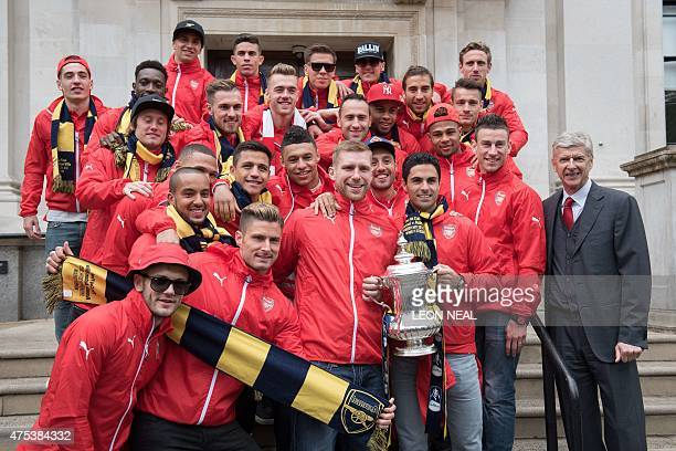 Arsenal's Spanish midfielder Mikel Arteta holds the FA cup trophy as the Arsenal squad pose outside Islington Town Hall during the Arsenal victory...