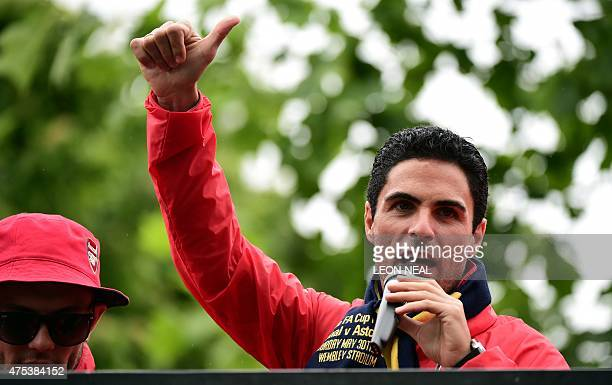 Arsenal's Spanish midfielder Mikel Arteta speaks to fans from an open top bus during the Arsenal victory parade in London on May 31 following their...