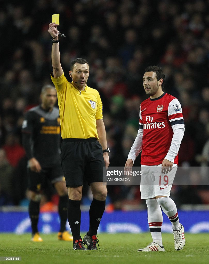 "Arsenal's Spanish midfielder Santi Cazorla (R) is shown the yellow card by referee Kevin Friend (L) during the English Premier League football match between Arsenal and Liverpool at The Emirates Stadium in north London on January 30, 2013. USE. No use with unauthorized audio, video, data, fixture lists, club/league logos or ""live"" services. Online in-match use limited to 45 images, no video emulation. No use in betting, games or single club/league/player publications."