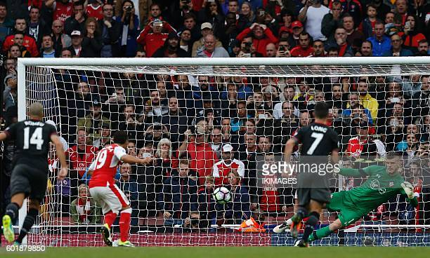 Arsenal's Spanish midfielder Santi Cazorla scores their second goal past Southampton's English goalkeeper Fraser Forster from the penalty spot during...