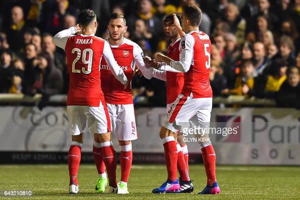 Arsenal's Spanish striker Lucas Perez celebrates with teammates after scoring the opening goal of the English FA Cup fifth round football match...