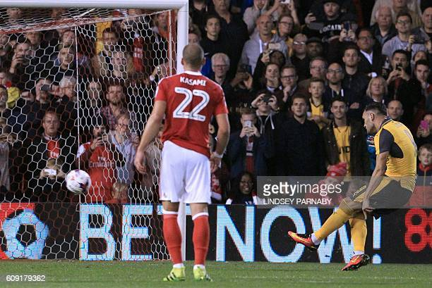 Arsenal's Spanish striker Lucas Perez scores their second goal from the penalty spot during the English League Cup third round football match between...