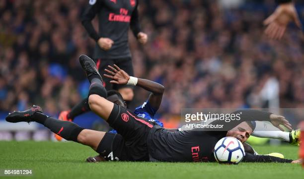 Arsenal's Swiss midfielder Granit Xhaka goes down in a challenge with Everton's Senegalese midfielder Idrissa Gueye during the English Premier League...