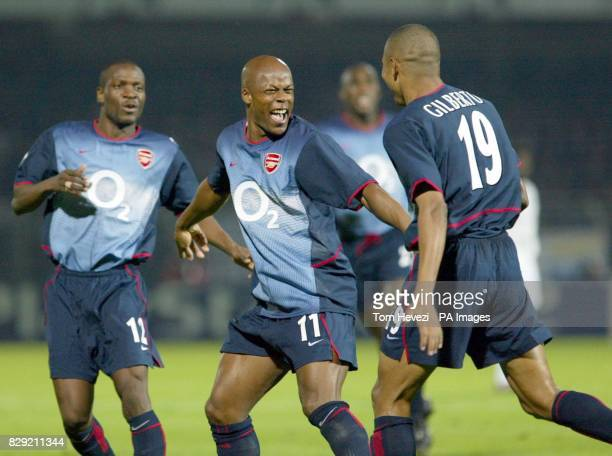 Arsenal's Sylvain Wiltord celebrates with Gilberto after he sets up the 1st goal against Auxerre for his team mate during their Champions League...