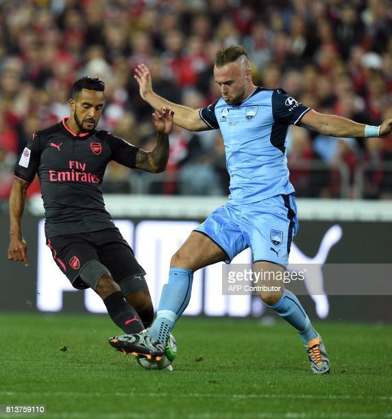 Arsenal's Theo Walcott and Sydney FC's Jordy Buijs fights for the ball during a preseason football friendly match against Sydney FC on July 13 2017 /...