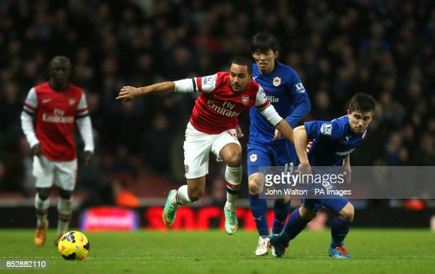 Arsenal's Theo Walcott battles for possession of the ball with Cardiff City's Declan John during the Barclays Premier League match at the Emirates...