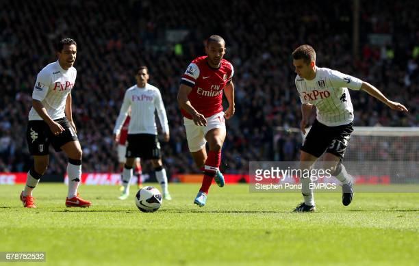 Arsenal's Theo Walcott breaks through pressure from Fulham's Kieran Richardson and Alexander Kacaniklic