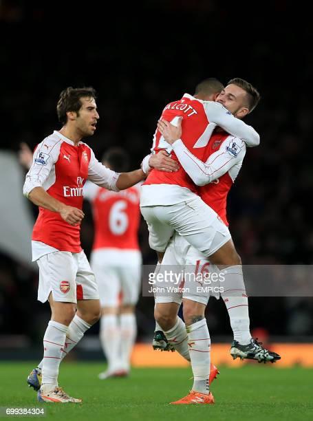 Arsenal's Theo Walcott celebrates scoring their first goal of the game with teammates Aaron Ramsey and Mathieu Flamini