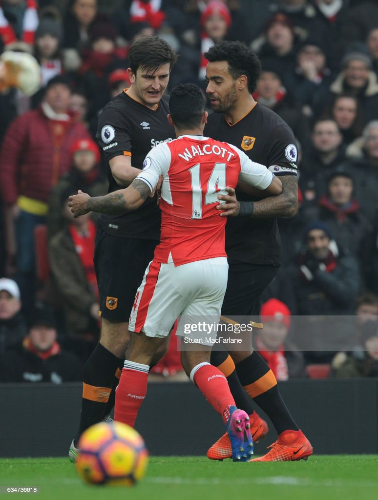 Arsenal's Theo Walcott clashes with (L) Harry Maguire and (R) Tom Huddlestone of Hull during the Premier League match between Arsenal and Hull City at Emirates Stadium on February 11, 2017 in London, England.