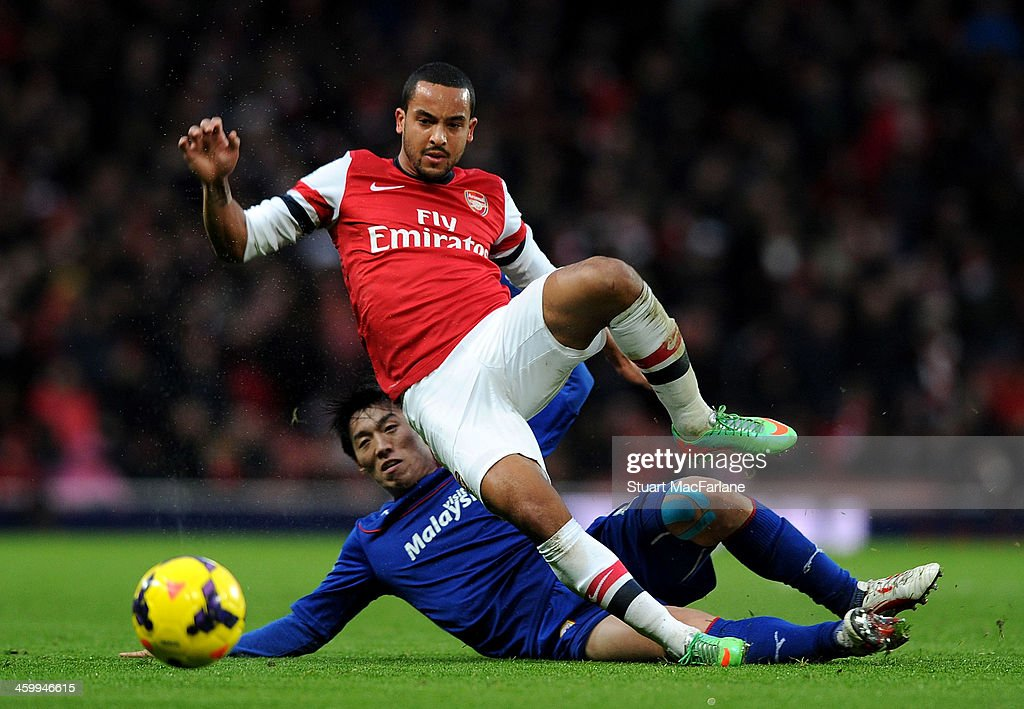 Arsenal's <a gi-track='captionPersonalityLinkClicked' href=/galleries/search?phrase=Theo+Walcott&family=editorial&specificpeople=451535 ng-click='$event.stopPropagation()'>Theo Walcott</a> is challenged by Bo-Kyung Kim of Cardiff during the match at Emirates Stadium on January 1, 2014 in London, England.