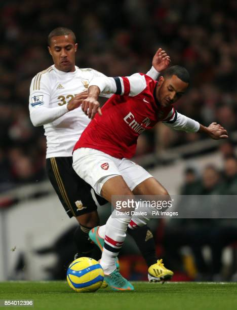 Arsenal's Theo Walcott is challenged by Swansea's Wayne Routledge during the FA Cup Third Round Replay at the Emirates Stadium London