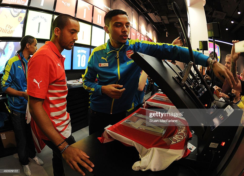 Arsenal's Theo Walcott is shown how to print his shirt by staff in the Armoury Store on July 11, 2014 in London, England.