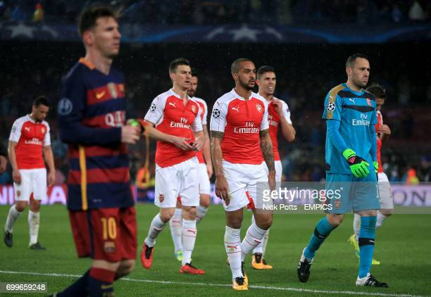 Arsenal's Theo Walcott leaves the field dejected with teammates after the final whistle beyond Barcelona's Lionel Messi