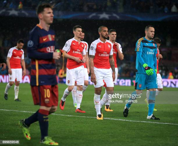 CROP* Arsenal's Theo Walcott leaves the field dejected with teammates after the final whistle beyond Barcelona's Lionel Messi
