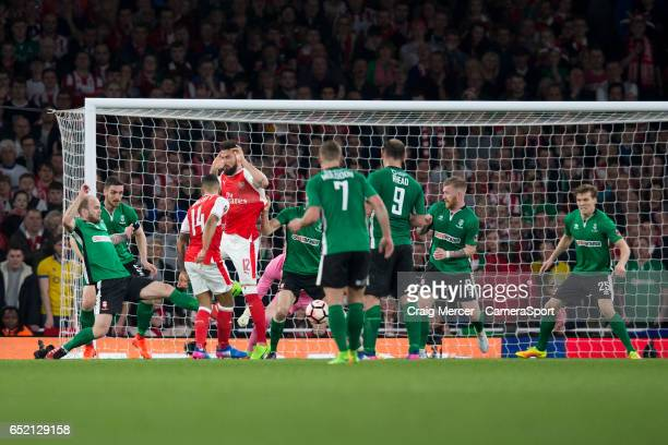 Arsenal's Theo Walcott scores the opening goal during the Emirates FA Cup QuarterFinal match between Arsenal and Lincoln City at Emirates Stadium on...