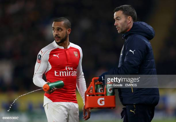 Arsenal's Theo Walcott sprays water on the ground